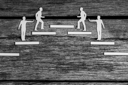 Group of paper cutouts striving for the same goal climbing steps in opposite directions towards the same platform in a conceptual greyscale image of competition.