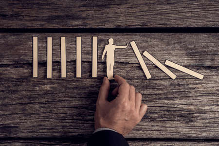 Retro image of businessman demonstrating stopping the domino effect using paper cut outs supported by his hands over rustic wood. Stock Photo - 87965605