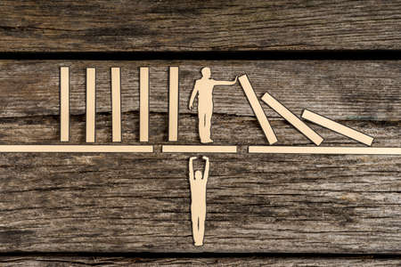 Teamwork and stopping the domino effect concept with paper cutouts of one man supporting a second on a bridge while he prevents a line of dominoes from falling over a rustic wood background.