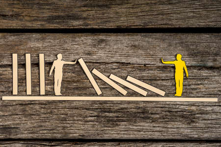 White silhouette cutout of a man holding up fallen blocks as yellow small person pushes blocks down over brown background.