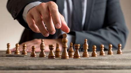 黒王に達するビジネス スーツを着ているビジネスマン木製のテーブルでチェスの駒。事業ビジョン、進行状況および成功の概念。