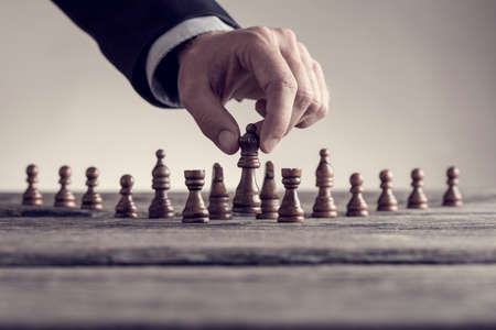 Retro image of a man playing chess moving the queen piece lifting it up in his fingers.
