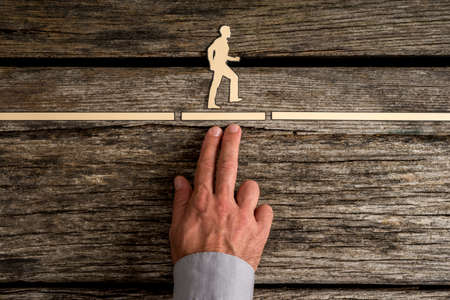 Business teamwork concept with the hand of a businessman supporting paper cut out of a man walking forwards to success over rustic wood background.
