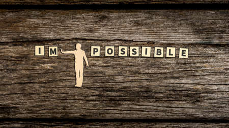 Impossible versus Possible concept with a paper cut out man pushing away the litters IM on a rustic weathered wood background.