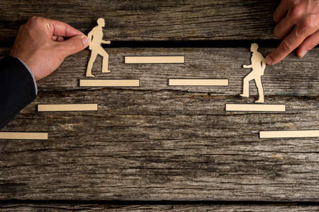 Two paper cutout men striving for the same goal climbing steps in opposite directions towards the same platform.