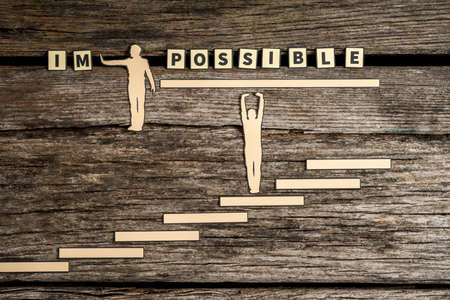 Impossible - Possible creative concept with two paper cutouts of men with one pushing away the letters IM while the second stands on steps supporting the rest of the text on a wooden background. Banco de Imagens