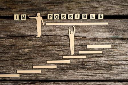 Onmogelijk - Mogelijk creatief concept met twee papieruitsparingen van mannen met één druk weg van de letters IM terwijl de tweede staat op stappen die de rest van de tekst op een houten achtergrond ondersteunen. Stockfoto - 89557067