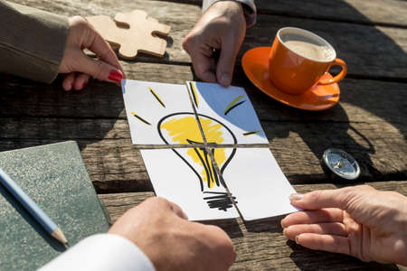 Brainstorming conceptual image of the hands of four business people putting together the pieces of a light bulb on a rustic wooden table outdoors in the sunlight. Imagens