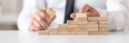 구조와 같은 계단으로 나무 못을 정렬하는 사업가의 근접 촬영. 비즈니스 비전 및 전략의 개념입니다.