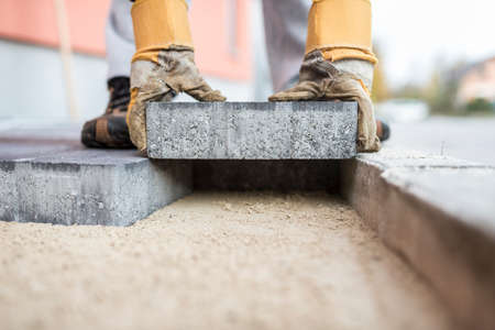 Close up of the gloved hands of a builder laying outdoor paving slabs on a prepared base. Stock fotó - 89442491