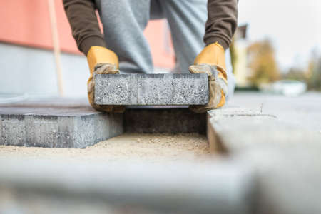Man laying a paving brick placing it on the sand foundation in a low angle view.