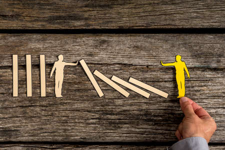 Silhouette cutout of a man holding up fallen blocks as yellow small person pushes dominoes down.