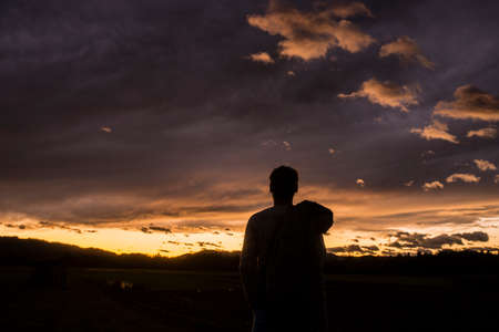 Silhouetted figure of a person against a sunset sky with fiery glow over the horizon and clouds. Stock Photo