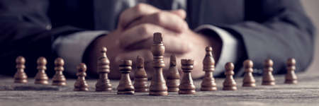 Retro style image of a businessman with clasped hands planning strategy with chess figures on an old wooden table. Stockfoto
