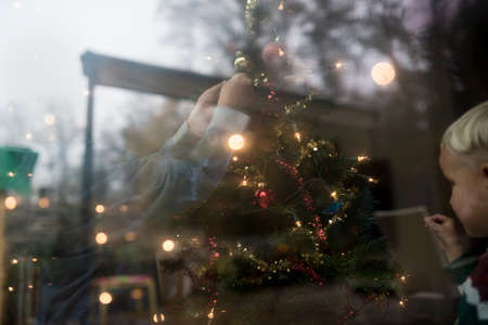 Young family decorating the Christmas tree indoors viewed through a large window with reflections of trees and the garden on the glass.