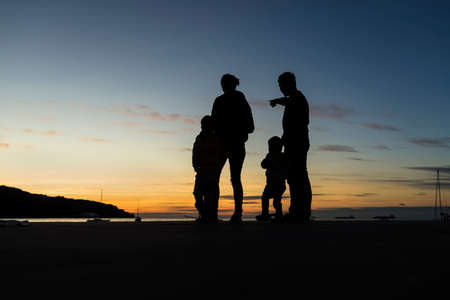 Silhouetted family outdoors looking at the sunset with the sea, mountain and sailboats behind in a rare view against evening sky. 版權商用圖片