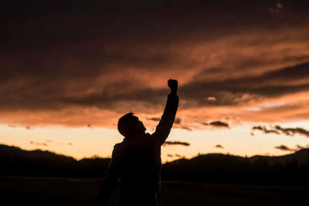 Jubilant man raising his fist silhouetted against a fiery orange sunset sky with clouds.