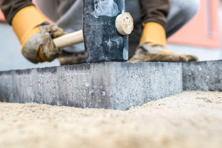 Builder tamping down a new paving slab or brick with a large mallet in a close up view on the hands and tool.