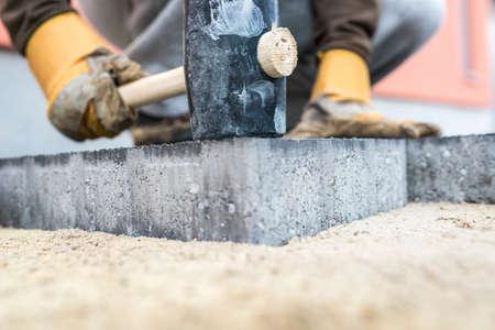 Erbauer, der eine neue Pflasterplatte oder einen Ziegelstein mit einem großen Holzhammer in einer nahen Ansicht über die Hände und das Werkzeug stopft. Standard-Bild