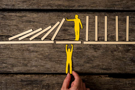 Yellow paper cutouts of one man supporting a second on a bridge while he prevents a line of dominoes from falling.