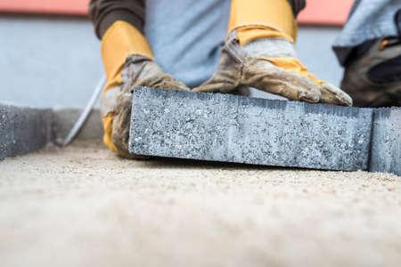 낮은 각도보기에서 낀된 손으로 모래 재단에 배치하는 포장용 슬 래 브 또는 벽돌을 누워 건축 계약자.