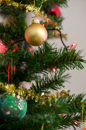 Golden bauble hanging from a decorated Christmas tree.