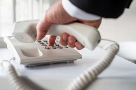Businessman dialing a telephone number in order to make a phone call.