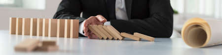 Wide panorama of a businessman stopping the domino effect by inserting his hand into a line of falling wooden blocks with a blueprint rolled alongside.