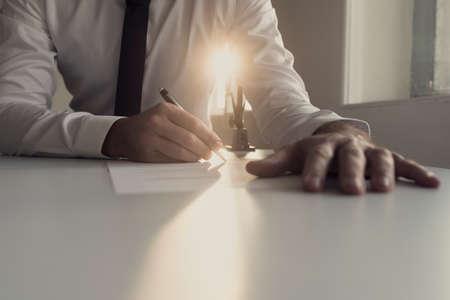 그의 손의 낮은 각도보기에서 밝은 햇빛의 샤프트에 의해 문서 백라이트를 서명하는 흰 셔츠에 사업가. 스톡 콘텐츠
