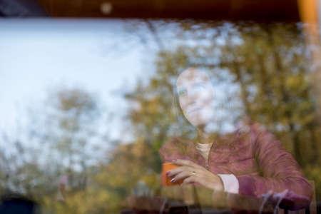 笑顔の女性とガラスに緑豊かな緑の木々 の反射表示ウィンドウとコピー スペースの後ろにコーヒーのカップ。