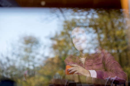 Reflections of leafy green trees on glass with smiling woman with cup of coffee visible behind the window and copy space. Stok Fotoğraf - 89006021