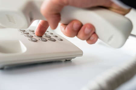 Closeup of businessman making a telephone call by dialing a phone number on a classical white landline device. Stock fotó