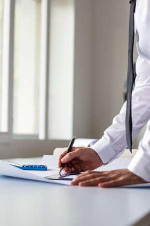 Architect, ontwerper of tekenaar werken met liniaal en potlood in het kantoor op een blauwdruk of plan in een lage hoek bekijken.