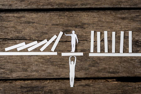 Creative teamwork and stopping the domino effect concept with paper cutouts of one man supporting a second on a bridge while he prevents a line of dominoes from falling over a rustic wood background.