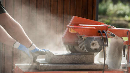 Side view of a man using an angle grinder or circular saw outdoors to cut through a block in a cloud of dust. Stock Photo