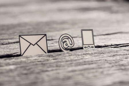 Imagen retro del concepto de comunicación empresarial con iconos para correo electrónico, una dirección web y teléfono en la mesa de madera rústica.