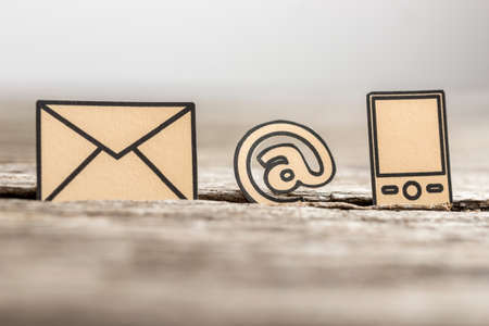 Small At sign, mail and phone symbols outlined with black stuck in between a crack in the wooden surface with blurry edges.