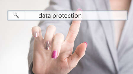 Woman touching a website navigation bar with the text data protection. Фото со стока