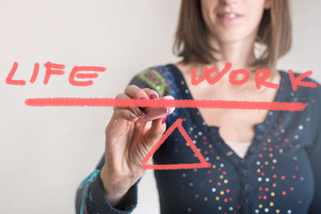 Life - Work balance concept with a young businesswoman drawing a seesaw with text on a glass or virtual screen in a close up view of her hand.