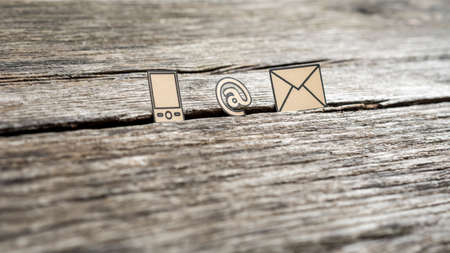 Contact icons at sign, mail and mobile phone outlined with black stuck in between a crack in the wooden surface. Stock Photo
