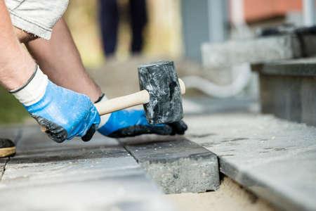 Werkman die een straatsteen of een baksteen legt aanstampen het neer met een grote houten hamer in een dichte omhooggaande mening van zijn handen.