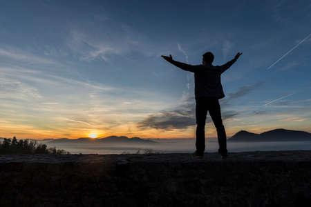 彼の腕を持つ男は立っている屋外コピー スペースと遠くの山々 を越えて覗く燃えるような太陽とカラフルな日の出を背景にシルエットを広く普及。