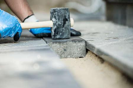 Bouwer die een straatsteen of een baksteen legt die het aanstampt met een rubberhamer.