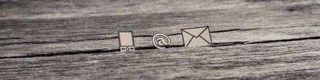 Szeroki, panoramiczny widok ikon na znak, poczty i telefonu komórkowego wetkniętych między pęknięcie w drewnianej powierzchni, stonowany efekt retro.