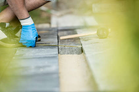 Builder measuring a gap for a new paving stone with a tape measure as he lays a new floor on a foundation of levelled sand with colored side vignette. Stock Photo