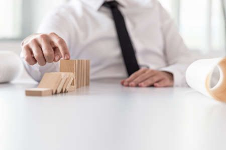 Businessman wearing white shirt and black necktie interrupting domino effect by stopping wooden dominoes bricks from crumbling.
