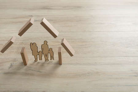 Real estate concept with a cut out of a family inside the shape of a residential house made of building wooden blocks. Stok Fotoğraf