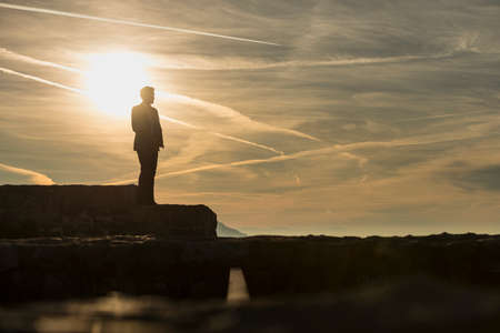 Businessman in a suit standing outdoors on a wall against a sunrise with copy space.