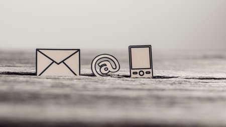 Communicatie pictogrammensentelefoon, bij teken en post, op geweven rustieke houten lijst, uitstekend effect gestemd beeld. Stockfoto