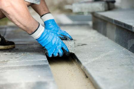 Contractant die nieuwe straatstenen of stenen legt, sluit omhoog mening van zijn gehandschoende handen. Stockfoto